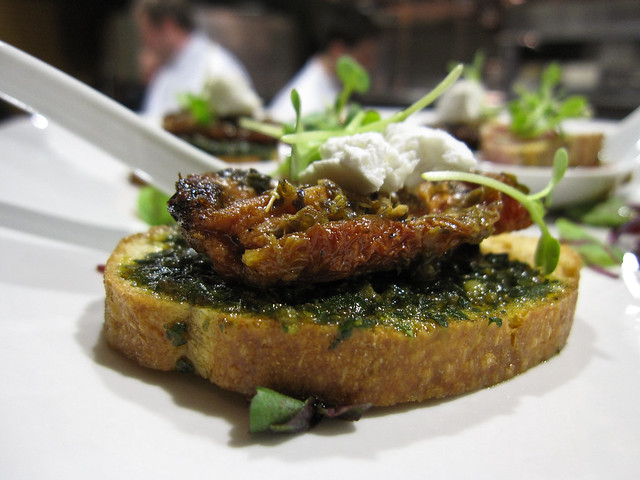 Crostini served with pesto, sun-dried tomato and goat cheese