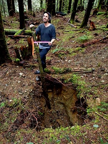 A volunteer stands over a septic field test hole near the trail