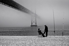 25th of April Bridge in the Mist (Gerald Verdon) Tags: leica bridge bw copyright mist men portugal fog fisherman haze europe fav50 lisboa lisbon voigtlander rangefinder fav20 nb m8 getty fav30 25deabril gettyimages verdon lisbonne ultron fav10 fav40 fav60 fav70 blackandwhiteonly ilustrarportugal allrightsreservedgraldverdon