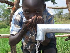 A young boy drinks clean water straight from the pump