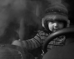 Behind the Wheel (L A Cooley) Tags: lighting winter light boy shadow portrait bw italy cloud baby white mist black rome roma cute eye lamp face hat wheel canon eos 350d mirror kid eyes italia driving silent child hand natural bn e mysterious stare driver reach florian dslr delicate gaze bianco nero steeringwheel albano alpharomeo147 knitbeany