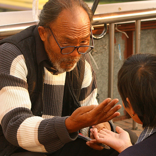 Palm reading in China: palm reader at work.