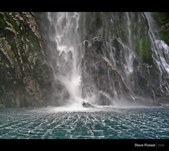 Falling Water (Steve Rosset) Tags: new travel blue sea newzealand green 2004 nature wet water face rain rock geotagged waterfall moss pattern power natural pacific vibrant south sightseeing azure rocky vivid fresh cliffs falling exotic zealand coastal backpacking sound tropical coastline leisure ripples milford february lush splash tasman milfordsound powerful fiord fiords global roaring australasia fiordland theunforgettablepictures steverosset visipix