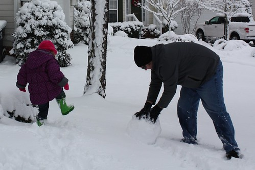 Dave starting a snowman, Catie stomping the snow
