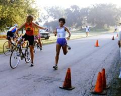 Team Handoff: End of Run > Start of Bike (danagraves) Tags: women earlymorning biker runner trafficcones houstontx swimbikerun asphaltroad teamhandoff