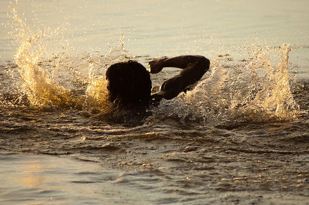 Un muchacho nada en el Río Jejuí cerca de la playa del Puerto La Niña en la tarde del Viernes Santo, durante la Semana Santa en San Pedro. (Elton Núñez - San Pedro, Paraguay)