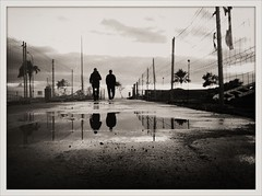 """The Long Walk on a (Post-Rain) Winter Afternoon"" (Sion Fullana) Tags: sea people urban blackandwhite bw espaa reflection blancoynegro clouds reflections puddle spain rainyday streetshots streetphotography silhouettes palmtrees nubes reflejo mallorca palma aftertherain siluetas allrightsreserved reflejos majorca iphone charco palmademallorca peoplewalking urbanshots traslalluvia iphone4 iphonephotography twomenwalking iphoneshots iphoneography iphoneographer sionfullana editedanduploadedoniphone throughthelensofaniphone"