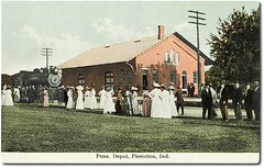 Pennsylvania Railroad Depot, Pierceton, Indiana (Hoosier Recollections) Tags: people woman usa signs man color men history industry station buildings walking clothing women hats indiana trains machinery transportation pedestrians depot businesses railroads kosciuskocounty pierceton hoosierrecollections