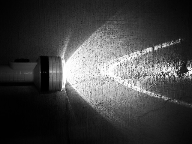 flash light or torch on painted block wall black and white