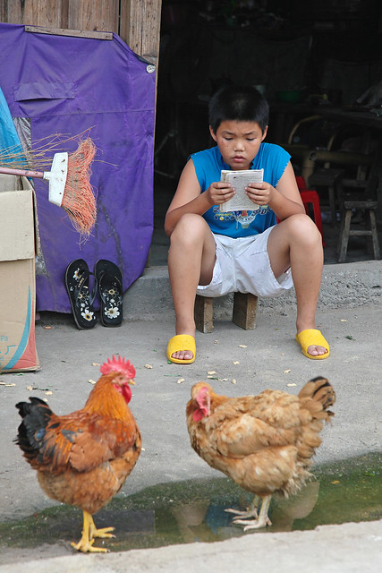 A boy studying on the street in Fuli village, China
