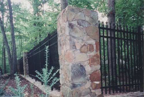 corner stone column of property border fence made of stone columns and iron