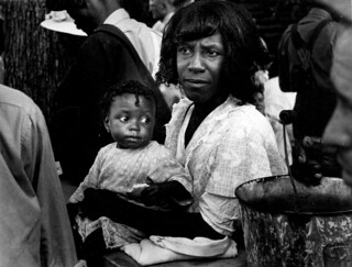 Black woman with child in her lap at STFU meeting.
