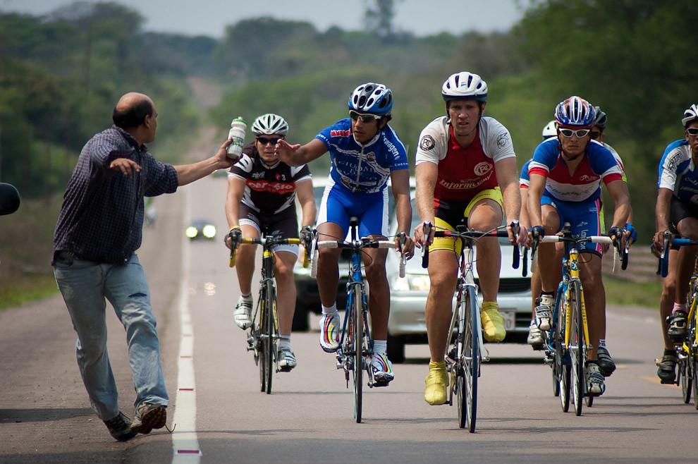 Un asistente pasa agua a uno de los competidores de la Copa El Colchonero González de la serie de carreras del campeonato nacional de Ciclismo que fue llevada a cabo el domingo 19 de setiembre, en modalidad ruta. Uno de los principales trayectos recorridos ese día comprende la ruta que une el Centro de Paraguarí con la Ciudad de Villarrica pasando por Sapucai. (Elton Núñez - Sapucai, Paraguay)