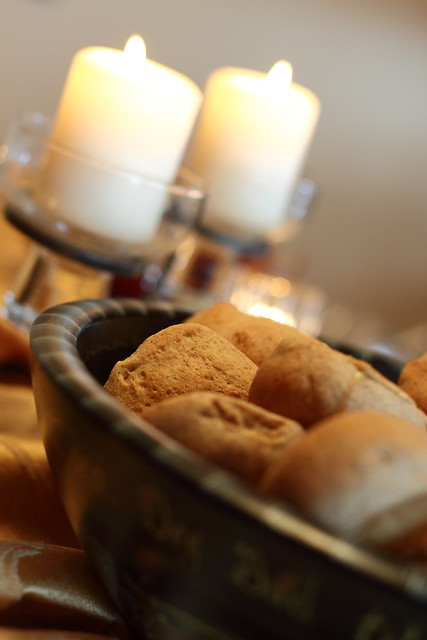 Dinner rolls in a bowl with candles in the background.