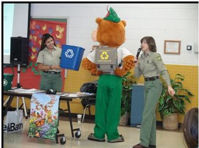 Sustainable Operations team member Maritza Huerta (L) and Tamberly Conway of Conservation Education explain Woodsy Owl's motto to K through 2 students at Braddock Elementary School.