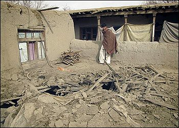 An Afghan youth looks at the damage caused during a NATO's forces raid in Khogyani district of Nangarhar province, east of Kabul, Afghanistan on Monday, Feb. 21, 2011. The NATO coalition says it is investigating the accidental death of Afghan civilians. by Pan-African News Wire File Photos