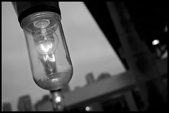 Granville Island illumination (Eric Flexyourhead) Tags: lighting city light sky urban bw canada detail glass lightbulb bulb vancouver grey blackwhite bc bokeh britishcolumbia illumination overcast clear granvilleisland incandescent filament fragment olympusep1 panasoniclumix20mmf17