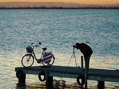 La puesta en escena (.Bambo.) Tags: sunset lake water bike atardecer agua bicicleta embarcadero ocaso fotgrafo laalbufera