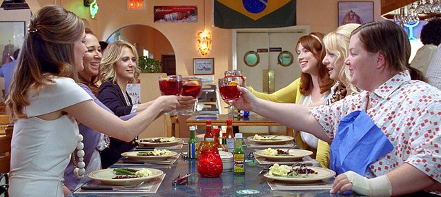 the cast of Bridesmaids, six women, around the table at a restaurant.