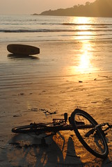 Bicycle on beach as sun sets for the day (amazing_tina) Tags: sunset sea water beautiful bicycle sand waves surfboard sunsetbeach sunsetting sunreflection purplesky palolembeach goabeach