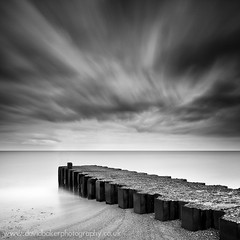 Land Stage (David_Baker) Tags: ocean county uk longexposure greatbritain sea england blackandwhite cloud seascape abstract motion beach water monochrome weather clouds mono coast pier blackwhite suffolk movement sand scenery solitude day view cloudy empty jetty horizon dramatic stormy nobody coastal coastline daytime lowtide seashore groyne eastanglia ledges