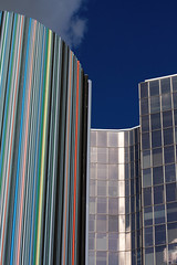 Contrasts - La Defence - Paris - France (tom.wright) Tags: city blue red sky orange cloud paris france colour building green window glass yellow vertical duct grey europe district pipe stripe line business raymond colourful curve defence striped ventilation ladefence tomwright businessdistrict canonefs1785mmf456isusm morretti copyright2010 raymondmorretti