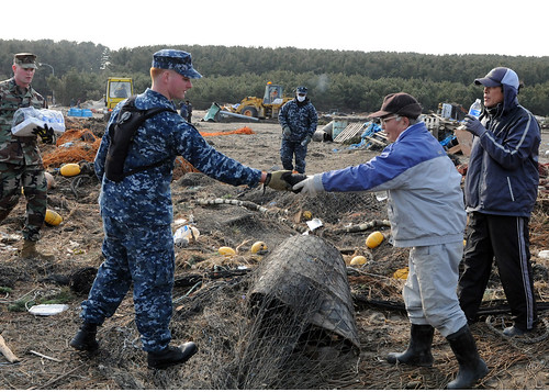Sailor returns netting to Japanese man during cleanup at Misawa, Japan following earthquake.