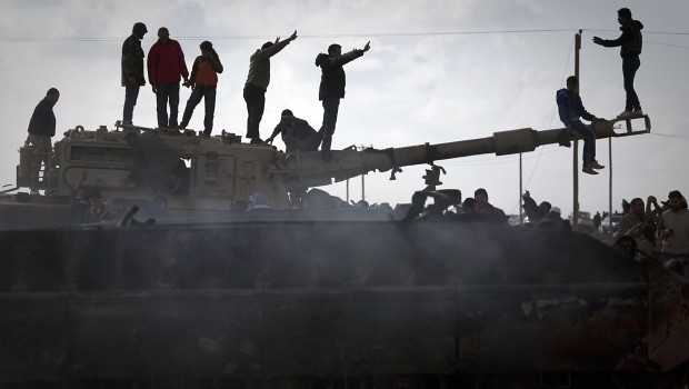 Libyan people celebrate on a knocked out Gadaffi tank