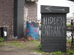 Hidden Entrance (Magic Pea) Tags: blue red urban streetart london sign photography graffiti canal photo chalk drum entrance container hidden kettle directions arrow hackney hazard hazardsign eastlondon hackneymarshes hiddenentrance magicpea