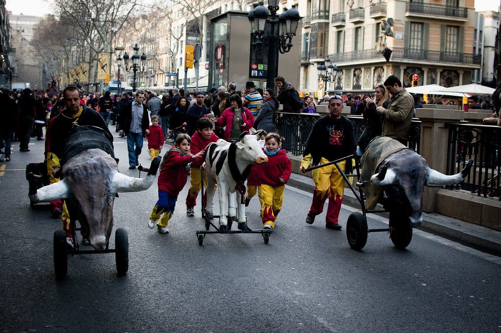 Kids running with a papier-maché cow