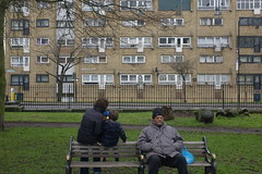 L1002202 woman child man on park bench in hackney east london uk (rafhuggins) Tags: park woman man black london bench child east council block hackney distance staring railings stoke newington noddy