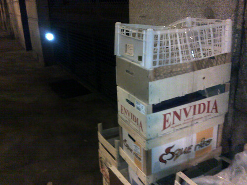 cajas de fruta vacías en la calle, en una de ellas se lee la marca: ENVIDIA