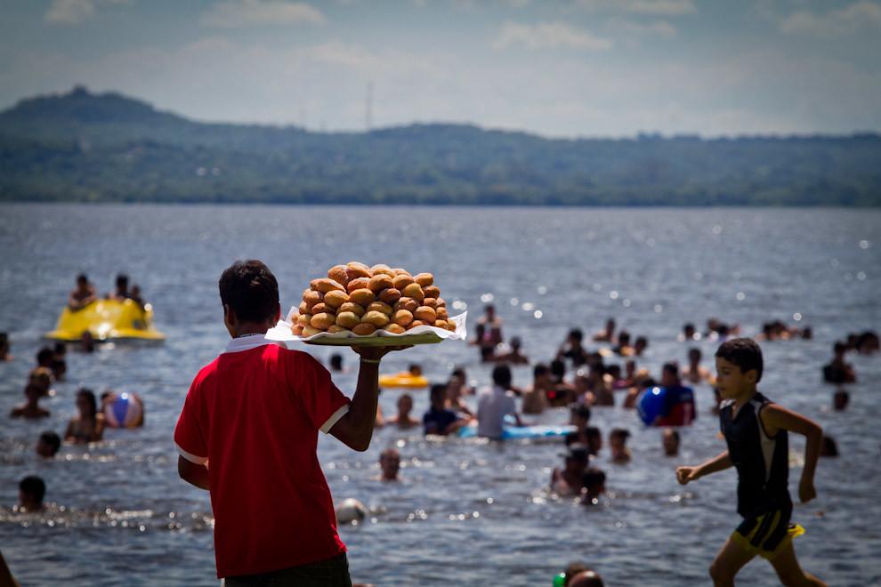 Un vendedor de bollos (un tradicional bocadillo relleno de dulce de leche o de guayaba) se pasea por una de las muchas playas, ofreciendo su producto, a los visitantes de la ciudad veraniega de San Bernardino, que acuden desde distintos puntos del país en los meses de enero y febrero. (Tetsu Espósito - Ypacaraí, Paraguay)