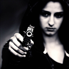 CLICK CLICK BOOM (Laura Galley) Tags: portrait blackandwhite woman blur girl dark fight dangerous war gun contemporaryart gothic young highcontrast monotone anger revenge weapon sultry grainy vixen blackangel lafemmenikita posd stealingshadows lauragalley