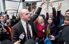 photo of a man in a crowd, he is holding his fist upraised