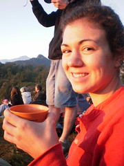 Stephanie DeHart enjoying a cup of hot chocolate while watching the sun rise over Lake Atitlan