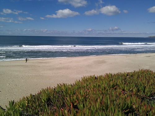 Surfer on the beach at Half Moon Bay