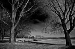 as brandon watched the ominous blackness envelop the sky, he failed to hear the three zombies coming up from behind.  look behind you... (lynn.h.armstrong) Tags: park camera trees sky bw white ontario canada black art ice water grass clouds dark lens geotagged photography photo spring interesting mac aperture nikon rocks long flickr zoom ominous south evil ground lynn h shore nikkor zombies armstrong markers stormont vr afs gettyimages dx farran sault ingleside 2011 ifed 18200mm f3556 attributionnoderivs vrii d7000 ccbynd lynnharmstrong requesttolicence