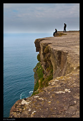 Cliffs of Moher (AlpineEdge) Tags: ocean uk travel ireland friends vacation sky cloud man adam water beautiful grass birds silhouette parish rock clouds standing europe sitting shadows natural ryan doolin eu roadtrip drop tourist cliffs worldheritagesite lichen cracks cliffsofmoher rockclimbing westcoast lichens atlanticocean shrubs moher liscannor cleave of 1millionvisitors