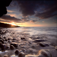 Sunset Clashach Cove (angus clyne) Tags: world ocean new old blue light sunset red cliff cloud sun seascape water stone silver dark landscape flow gold bay coast scotland long exposure angle bright time angus cove tide north wide scottish east pebble rig oil sail cave 20mm surge swell dri moray firth lossiemouth clyne hopeman digitalcameraclub colorphotoaward clashach vertorama covesea 100commentgroup canon5dmarkii