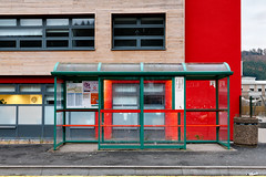 Crosskeys Bus Stop (Steve Ellaway) Tags: street windows red urban detail college glass lines wales architecture composition contrast buildings evening community village squares pavement stripes empty transport shapes documentary boring sidewalk busshelter views vernacular local form walls welsh geography streetfurniture roads juxtaposition deserted banal compare rectangles valleys perspex busstops crosskeys topographics facia welshvalleys coleggwent gwentcollege