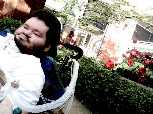 Nick sitting in front of flowers outside, in wheelchair
