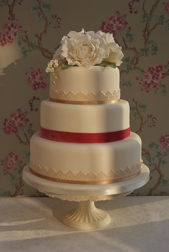Three tier wedding cake with peonies and lily of the valley topper