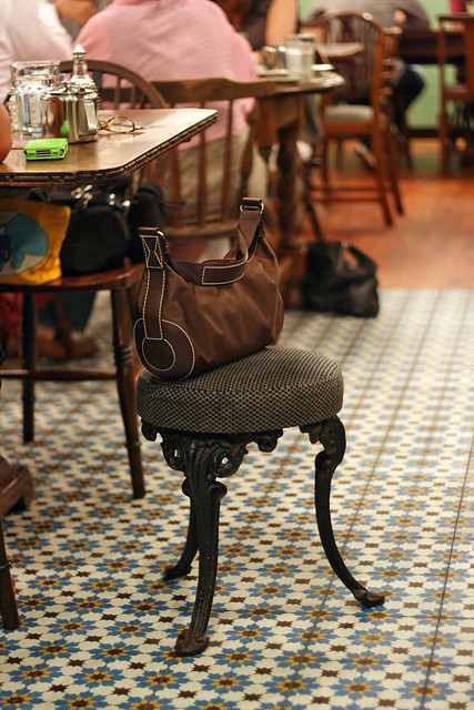 Eclectic furniture, handbag stools, and vintage floral tiles