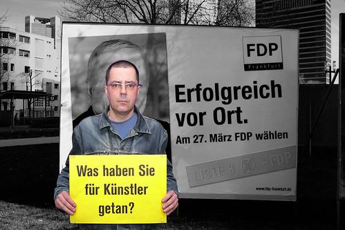 Aktion Was haben Sie für Künstler getan? vor FDP Plakat. Kommunalwahl Frankfurt März 2011