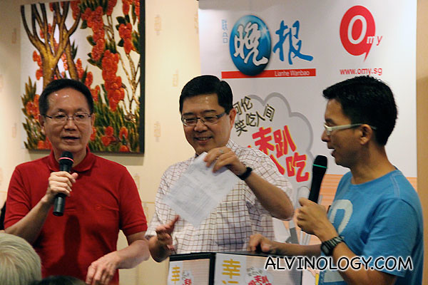 The boss of East Ocean Restaurant (centre) picking the lucky draw winners