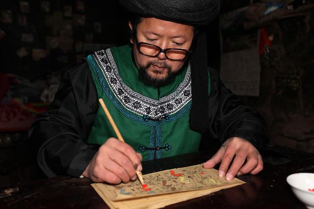 尔苏图画文字传承人杨德隆在书写历书《虐曼史达》