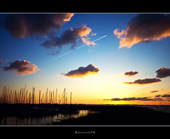 High Speed @ Sunset  .  .  .  [explored] (Borretje76) Tags: blue light sunset sun white haven black water netherlands dutch yellow clouds plane airplane boats boot iso100 boat zonsondergang blauw moody harbour yacht sony stripe trails wolken sigma boten explore trail sail mast f56 1020mm frontpage geel zwart wit enschede zon vliegtuig wolk lighttrail sfeer jachthaven masten explored jachten a580 gupr borret
