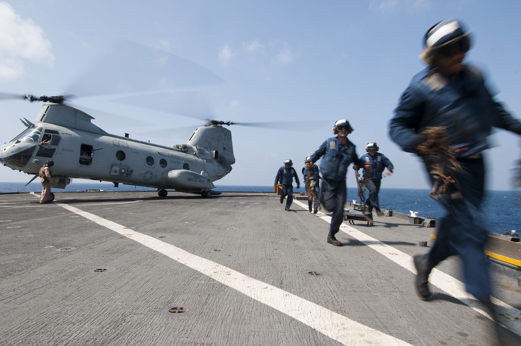 Flight deck personnel clear the deck before helicopter takes off from USS Comstock.