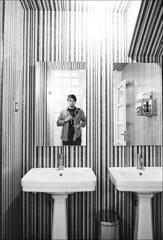 striped walls and checked shirt (gorbot.) Tags: barcelona blackandwhite bw selfportrait me bathroom mirror cafe raw reflected f4 dng leicam8 digitalrangefinder ltmmount voigtlander21mmcolorskoparf4